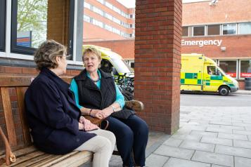 Two ladies talking outside a hospital with an ambulance behind them