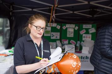 Healthwatch staff member taking down notes from a member of the public