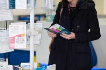 A lady looking at leaflets from a leaflet stand