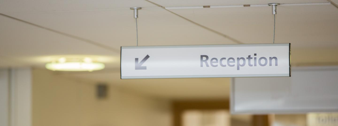 Sign saying reception hanging from waiting room ceiling
